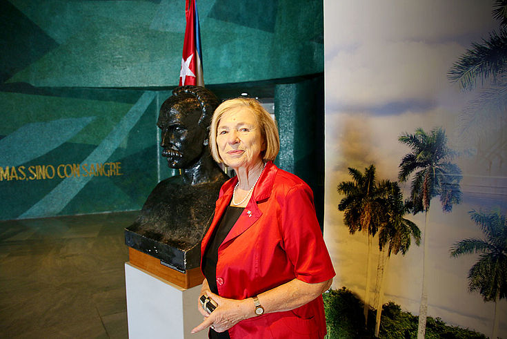 Ursula Männle vor der Büste. Im Hintergrund Palmen.