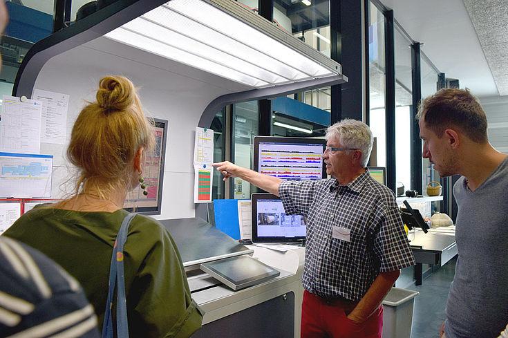 In einer Druckerei zeigt ein Werker gerade, wie alles funktioniert. Junge Menschen stehen drumrum.