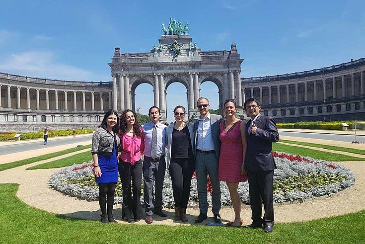Gruppenbild in einem hübschen Park mit umrahmendem Säulengang im Hintergrund