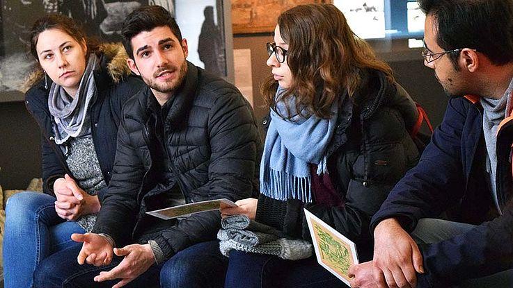 Einige der Studenten diskutieren offenbar angeregt. Ein junger Mann in der Mitte der Gruppe scheint, gerade ein Argument darzulegen. Blickt um Zustimmung heischend um sich.