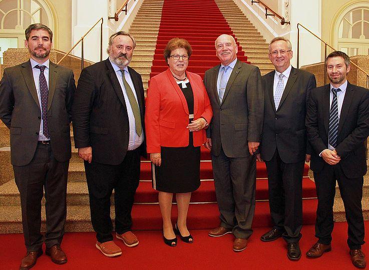 Gruppenbild vor Treppe mit rotem Teppich und viel Marmor.
