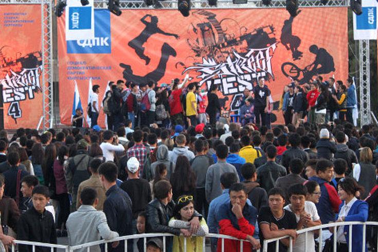 Wahlkampf in Kirgisistan: Zuschauer vor einem Podium mit Wahlkämpfern, dahinter Wahlplakate