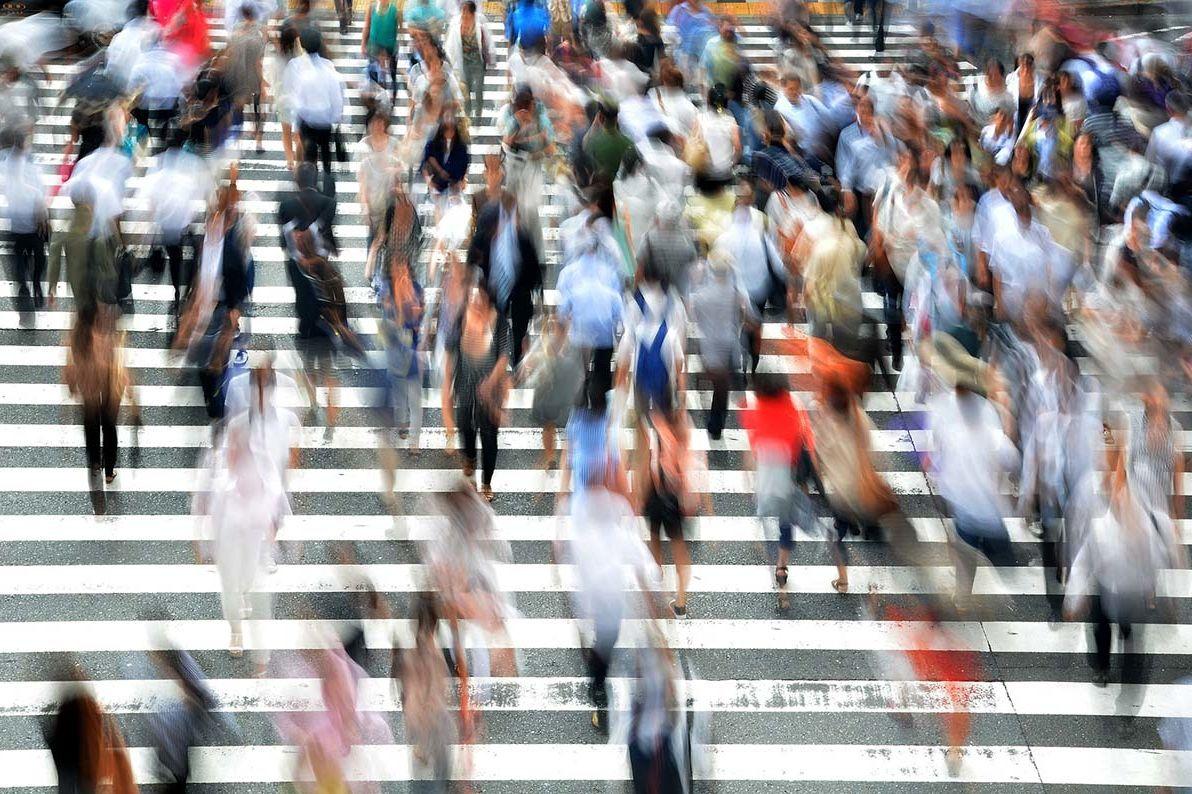 Viele Menschen gehen über eine Kreuzung.