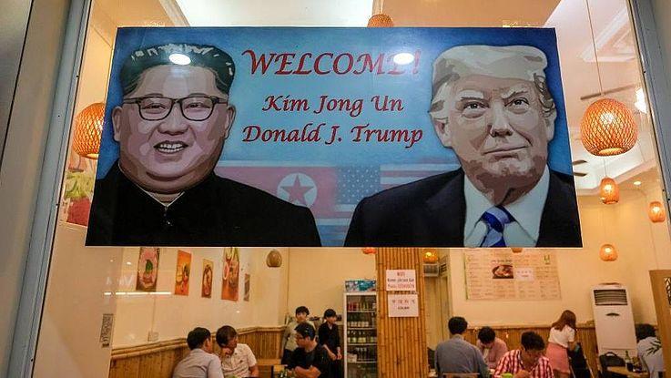 Auf einem riesigen Plakat sind Kim Jong-Un und Donald Trump abgebildet; das Plakat hängt in einem großen Saal