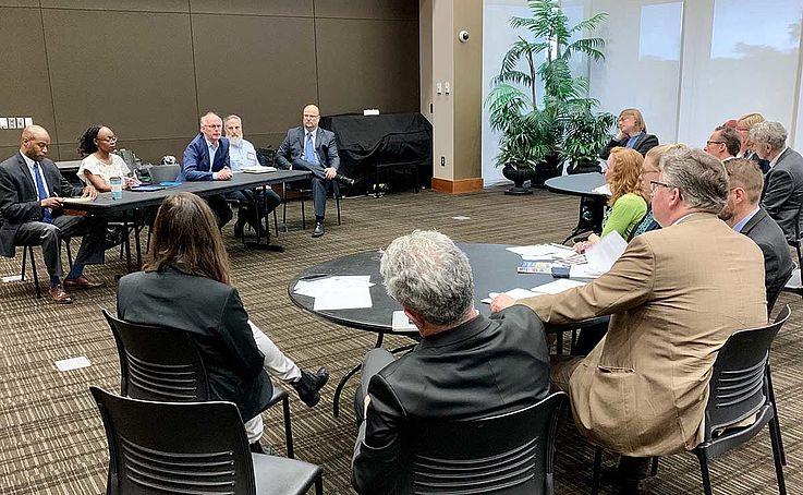 Konferenzraum mit Menschen, die im Kreis sitzen. Unterlagen, Papier, Gespräche