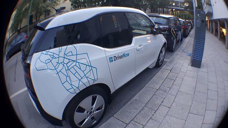 Ein Elektro-BMWi3 steht an einer Ledesaüle und wird mit Strom versorgt