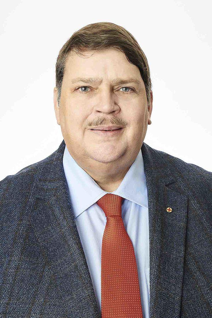 Mann mit schmalem Schnauzbart, rundem Gesicht, beleibt, Seitenscheitel.