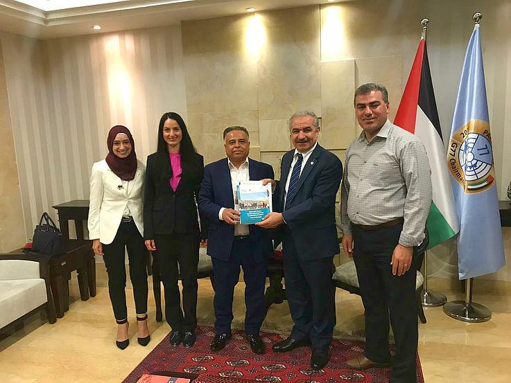 Der Premierminister der Palästinensischen Autonomiebehörde, Dr. Stayyeh, (2.v.r.) begrüßte ausdrücklich die gemeinsamen Aktivitäten der HSS vor Ort und der Gemeinde Ajja. Zwei Frauen und drei Männer stehen in einer Reihe. Die beiden Männer in der Mitte halten eine Broschüre.