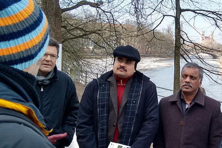 Teilnehmer der Delegation hören einem Mitarbeiter des Wasserwirtschaftsamtes zu, der über die Renaturierung der Isar berichtet. Im Hintergrund ist die Isar zu sehen.