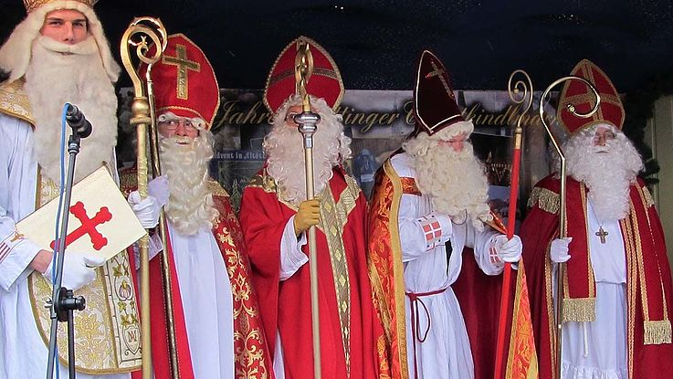 Fünf Nikolause in voller Festmontour mit Stäben, Mänteln und Bärten
