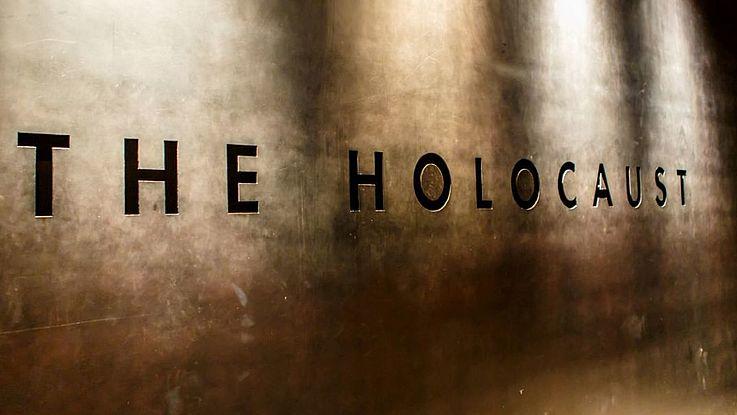 """Die Lettern """"THE HOLOCAUST"""" eingraviert auf einer großen Messingplatte in einer Gedenkstätte."""