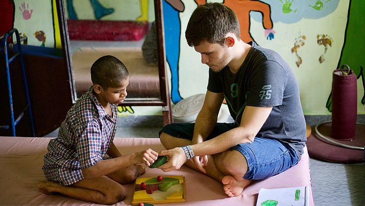 Junger Mann spielt mit indischem Kind