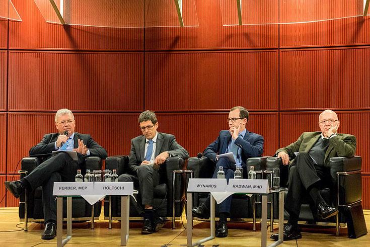 Vier Herren auf dem Podium. Markus Ferber (ganz links) spricht gerade ins Mikro.