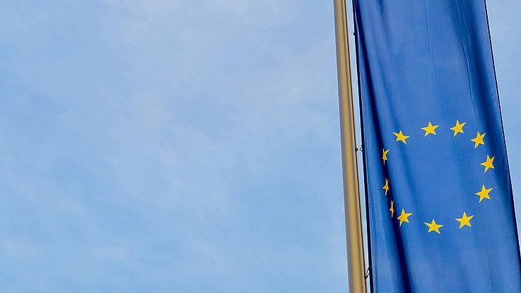 EU-Flagge an einem Fahnenmast, darüber der Himmel
