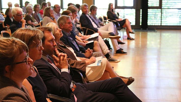 Menschen von der Seite wie sie sitzend einem Redner zuhören