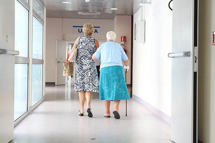 Alte Dame wird von jüngerer Dame einen Gang in einem Krankenhaus entlanggeführt.