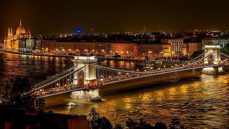 Budapest bei Nacht. Eine steinerne Brücke spannt sich über die Elbe. Im Hintergrund eine Kathedrale und repräsentative Bauten.