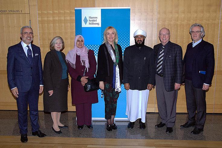 Gruppe der Gäste und Ursula Männle vor einer Fotostellwand der HSS