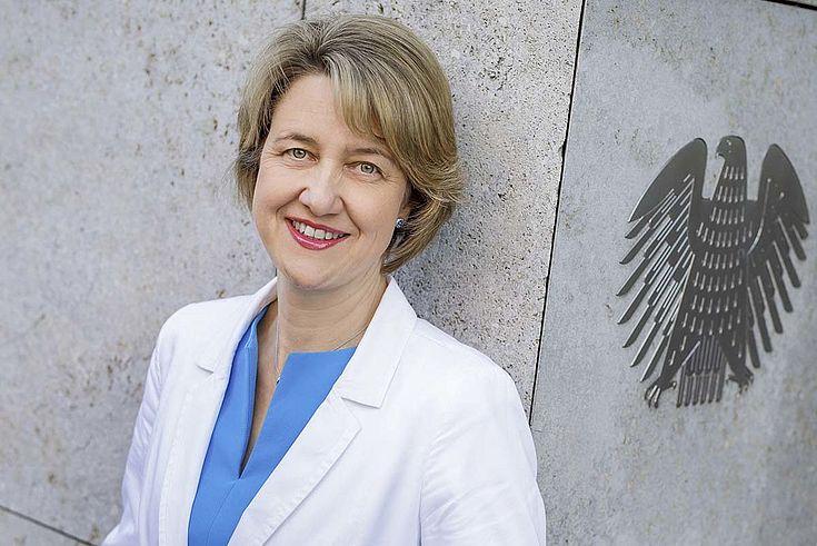 Weisgerber, eine freundlich lächelnde Frau, lehnt an einer Ecke des Bundestagsgebäudes neben einem metallenen, in die Gebäudewand eingelassenen Bundesadler.