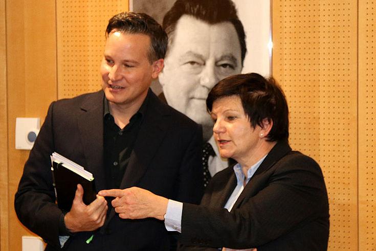 Gutjahr, sportlicher Anzug und Haarschnitt, und Weidenfells, klassisch seriös gekleidet, vor einem Bild von F.J. Strauß in ein Gespräch vertieft.