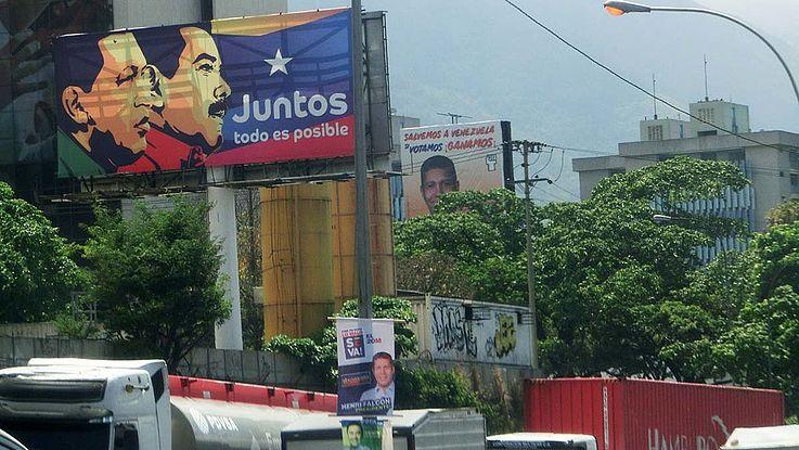 Straße mit übermäßig vielen Wahlplakaten. Auf dem zentralen das schneidige Gesicht Maduros und Hugo Chavez im Profil.