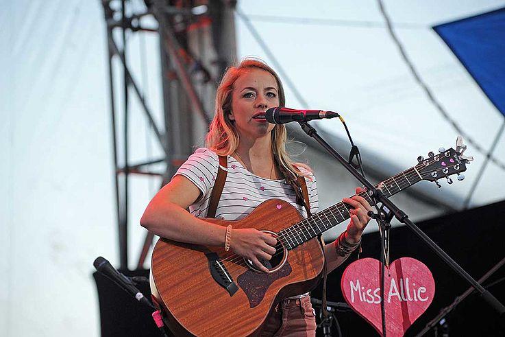 """Junge Frau mit Blümchen-T-shirt und Gitarre nebst rotem """"Wiesenherzl"""" auf dem """"Miss Allie"""" steht auf der Bühne."""