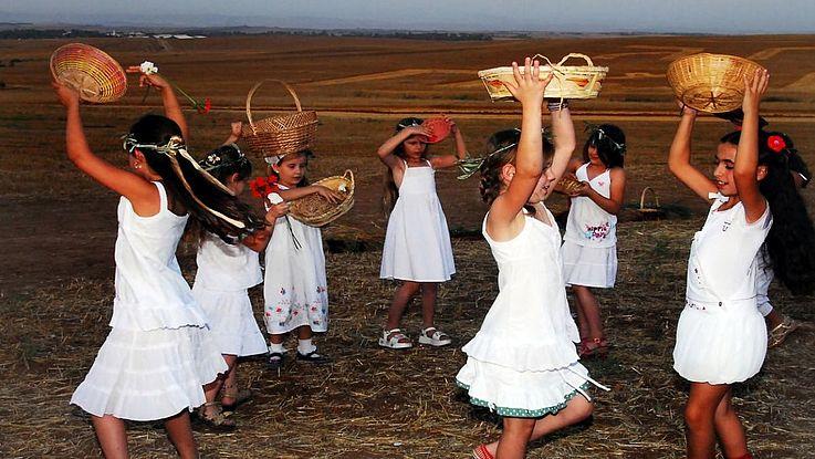 Junge Mädchen tanzen in einem abgeernteten Weizenfeld.