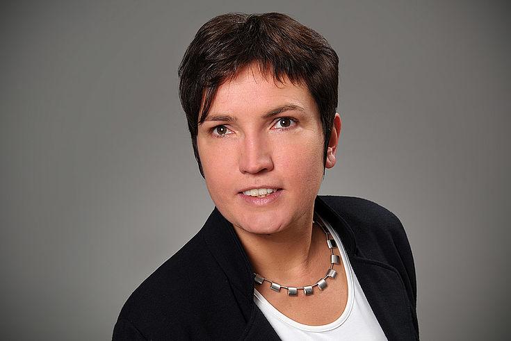 Forsch aus dem Foto blickende jüngere Frau mit energetischem Kurzhaarschnitt, schlichter Jacke und dezenter Halskette