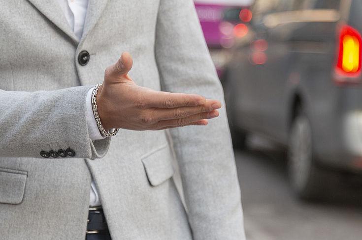 Eine zur Seite zeigende Hand, am Rand ist ein Auto zu sehen.