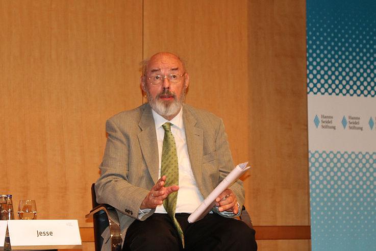 Sitzt in sich ruhend im Panel: Älterer, kleinerer, untersetzter Mann mit weißem Vollbart und Glatze.