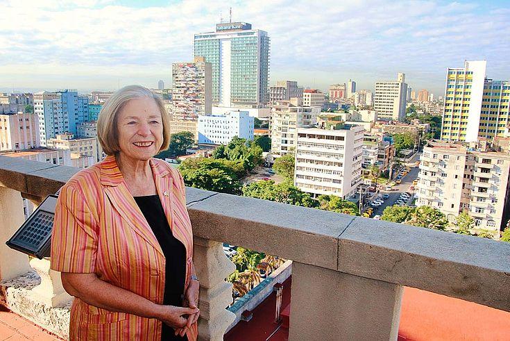 Ursula Männle steht auf einem Balkon, hoch über den Dächern Havannas. Im Hintergrund höhere Wohngebäude und ein gläsern verschalter Büroturm.