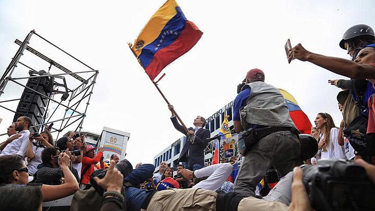 Guaidó schenkt die Flagge Venezuelas in mitten begeisterter Anhänger und Fotografen. Darüber der Himmel, an dem dunkle Wolken ziehen.