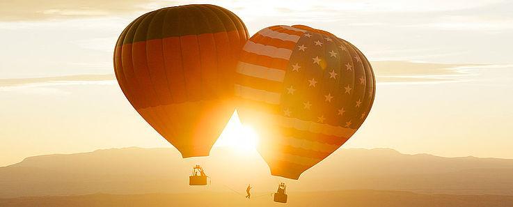 Zwei Fesselbalons aneinander in der Luft. Der rechte mit den stars und stripes der amerikanischen Flagge, der linke mit der Deutschlandflagge bemalt.