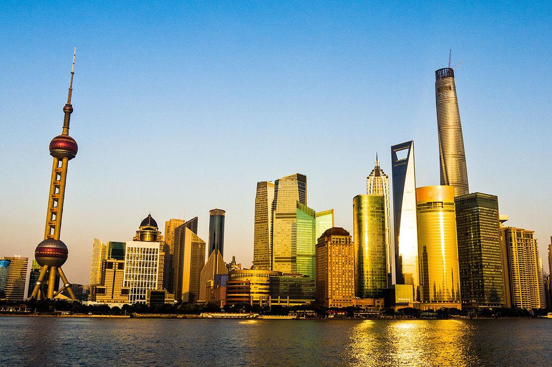 Skyline von ... Shanghai?... hohe Türme, Wolkenkratzer und ein spektakulärer Fernsehturm hinter einem Wasser.