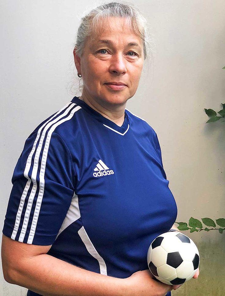 Friederike Pfaffinger im Fußballtrikot des Vereins, hält einen kleinen Fußball in der Hand und blickt in die Kamera.