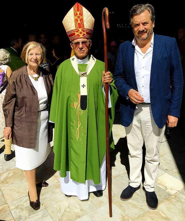 Ursula Männle steht links neben einem eindeutigen Erzbischof mit typischem Bischofshut und Kromstab. Mann in Blazer rechts daneben.