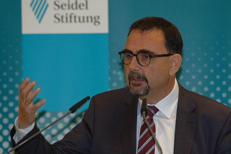 Mann mit Bart und Brille gestikuliert am Rednerpult