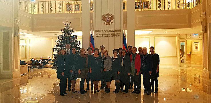 Gruppenbild in einem marmorgetäfelten Saal mit einem Weihnachtsbaum im Hintergrund