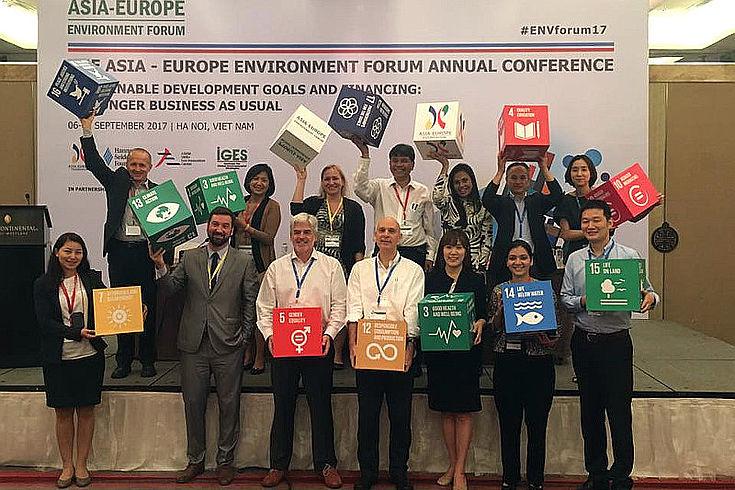 Wissenschaftler, Vertreter der Eine Gruppe von Wissenschaftlern, Vertretern der Zivilgesellschaft und des Privatsektors zeigen bei dem Forum Optimismus. In den Händen halten sie Würfel mit den verschiedenen Symbolen der Nachhaltigkeitsziele.