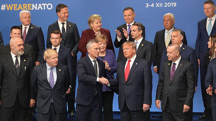 Die Staatschefs auf dem großen Podium. Donald Trump schüttelt in der Mitte mit finsterer Miene Hände.