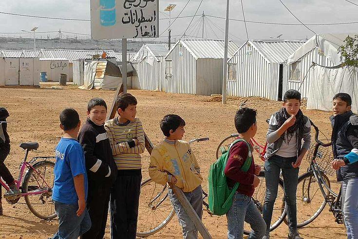 Kinder stehen am Rand des Lagers herum. Viel Sand. Im Hintergrund die dürftigen Zelte