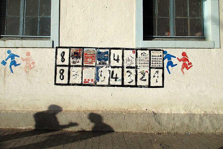 Eindrucksvolles Bild eines länglichen Wahlplakates an einer Hauswand zwischen zwei dunklen Fenstern. Auf der Hauswand zeichnen sich die Schatten zweier Personen ab, die sich offenbar gerade unterhalten.