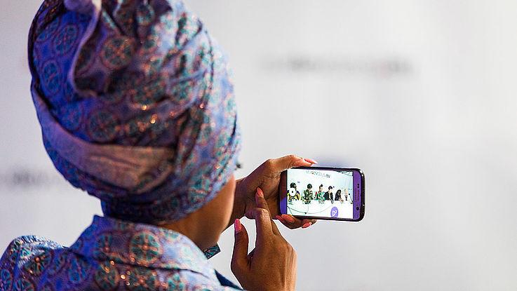 Dame mit hoch getürmten Kopftuch. Oberkörper von hinten aufgenommen. In der Hand hält sie ein Smartphone, auf dem ein Pannel zu sehen ist.