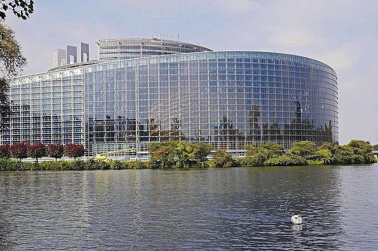 Das runde, gläserne Gebäude des EU-Parlaments an einem Wasser.