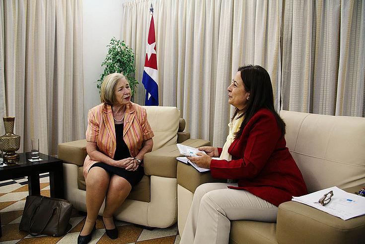 Ursula Männle im Gespräch mit Inalvis Bonachea auf zwei gemütlichen Sesseln. Im Hintergrund steht eine Flagge Kubas.