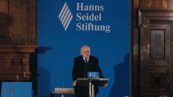 Mann an Rednerpult vor Logo der Hanns-Seidel-Stiftung