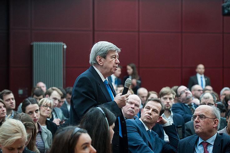 Älterer Herr erhebt sich im Plenum, um eine Frage zu stellen. Die Gäste in seiner Umgebung schauen interessiert zu ihm auf.