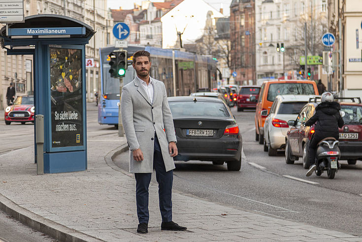 Junger Mann steht, von Kopf bis Fuß sichtbar auf einer Verkehrsinsel mit Haltestelle und vefahrender Straße.