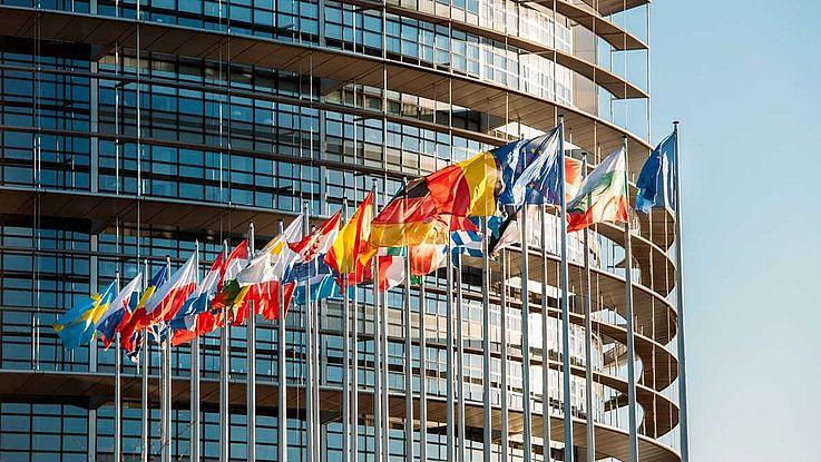 Ein großes, rundes Gebäude aus Glas und Stahl mit den Flaggen der EU-Mitgliedsstaaten davor, die im Winde wehen.