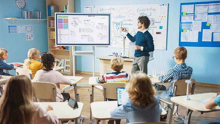 Eine Schulklasse. Der Lehrer erklärt an der Tafel etwas.